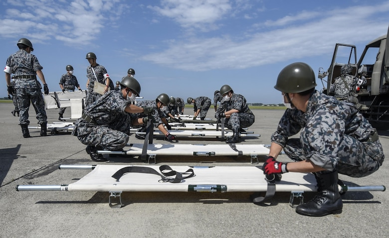 Japan Air Self Defense Force personnel prepare litters during a bilateral emergency management exercise at Aug. 31, 2016. USAF and JASDF agencies including security forces squadrons, medical and fire departments responded to approximately 60 USAF and Japanese personnel who simulated various injuries that could occur after an explosion. (U.S. Air Force photo by Airman 1st Class Sadie Colbert)