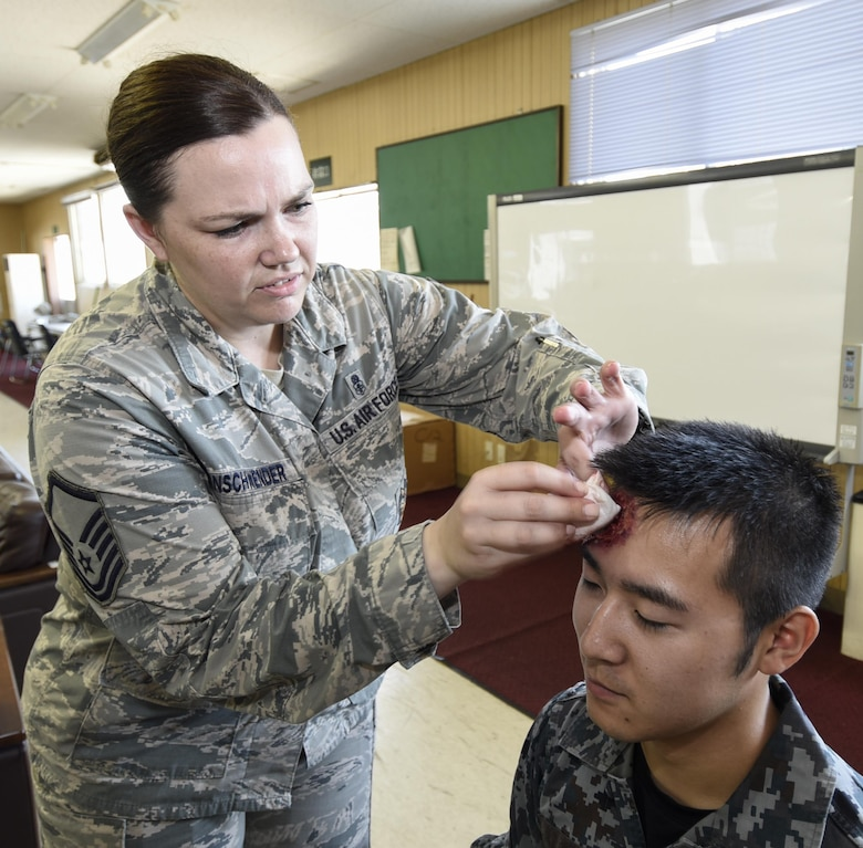 U.S. Air Force Master Sgt. Elizabeth Ehrnschwender, a wing self-assessment program manager with the 35th Fighter Wing staff agencies inspector general's inspections office, left, applies moulage to Japan Air Self Defense Force Senior Airman Ken Tanaka prior to the start of a bilateral emergency management exercise at Misawa Air base, Japan, Aug. 31, 2016. Approximately 60 service members participated in the exercise to simulate injuries for medical staff to diagnose and respond to. (U.S. Air Force photo by Airman 1st Class Sadie Colbert)