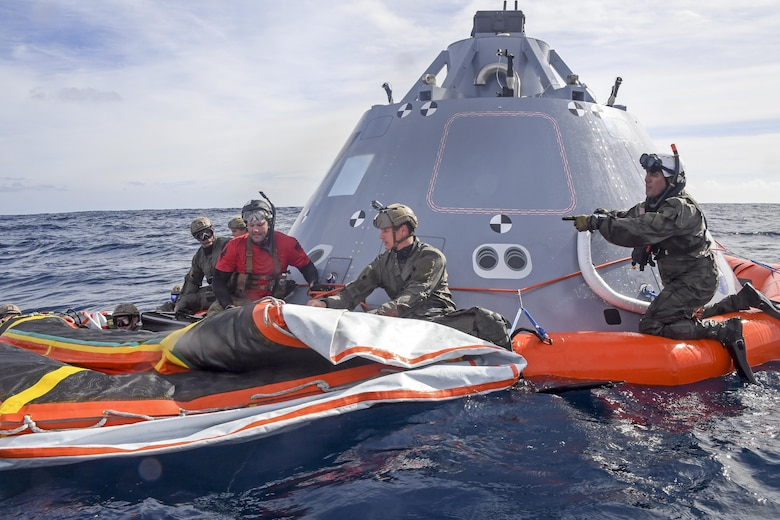 Master Sgt. Jermey Diola (right), a Para-Rescue Jumper assigned to Air Combat Command, instructs Navy Divers assigned to Explosive Ordnance Disposal Mobile Unit 3 and Mobile Dive and Salvage Company 3‐1 on the boilerplate-testing article, belonging to NASA's Orion Program, in the Pacific Ocean, Oct. 31, 2016. USS San Diego (LPD 22) is currently conducting recovery and towing techniques utilizing NASA and Naval technology with the goal of reducing manning and increasing safety. (U.S. Navy Combat Camera photo by Petty Officer 3rd Class Alfred A. Coffield)