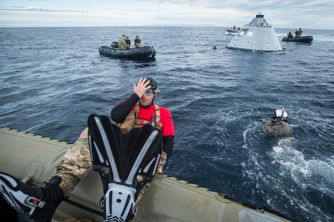 Tech Sgt. Shane Brickey, assigned to the 88th Test and Evaluation Squadron (53rd Wing, Air Combat Command), dives in the Pacific Ocean to retrieve a boilerplate-testing article, belonging to NASA's Orion Program, Oct. 28, 2016. USS San Diego (LPD 22) is currently conducting recovery operations with NASA's Orion Program; testing a new towing technique utilizing NASA and Naval technology with the goal of reducing manning and increasing safety. (U.S. Navy Combat Camera Photo by Petty Officer 1st Class Torrey W. Lee)
