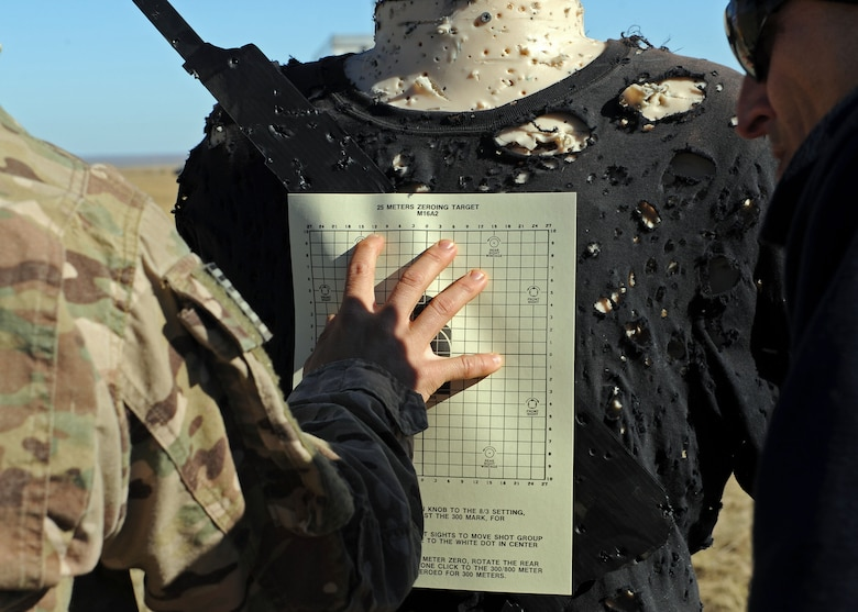 A member of the 27th Special Operations Civil Engineer Squadron Explosive Ordnance Disposal flight adheres a sighting target to a Robotic Human Type Target prior to conducting live fire training Nov. 8, 2016, at Melrose Air Force Range, N.M. RHTT targets are autonomous and smart in nature, allowing for the creation of infinite realistic scenarios which call for Air Commandos to employ elevated tactical thought processes, and execute appropriate courses of action with real-time urgency. (U.S. Air Force photo by Staff Sgt. Whitney Amstutz/Released)