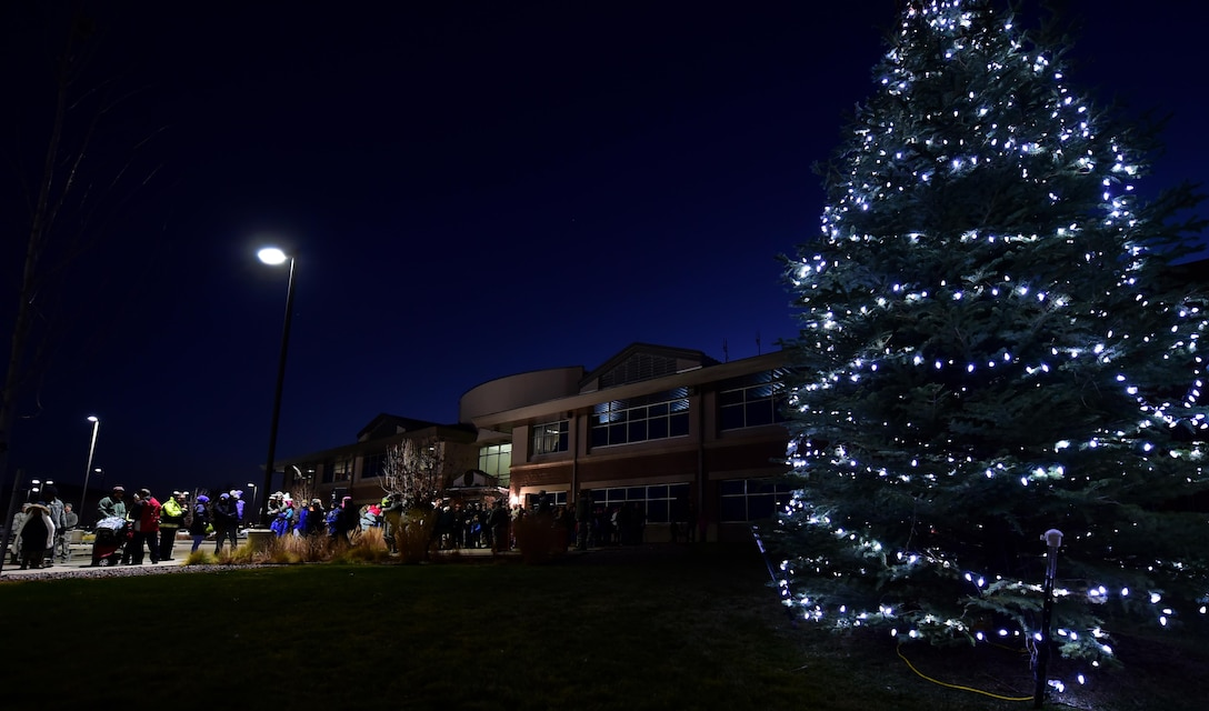 Members of Team Buckley gather at the 460th Space Wing Headquarters building for the annual Christmas tree lighting ceremony Nov. 30, 2016, on Buckley Air Force Base, Colo.  The tree lighting ceremony included refreshments, carolers and even a visit from Santa Claus. (U.S. Air Force photo by Airman Holden S. Faul/ Released)