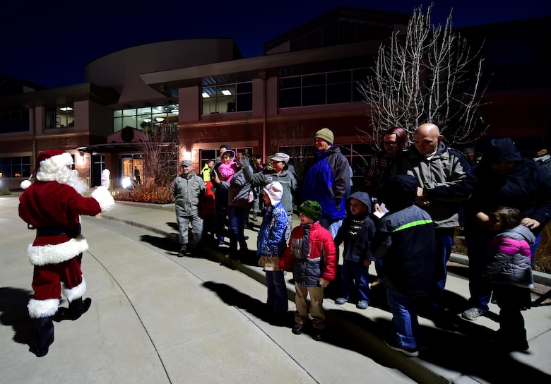Families from Team Buckley welcome Santa during the annual Christmas tree lighting Nov. 30, 2016, at the 460TH Space Wing Headquarters building on Buckley Air Force Base, Colo. After meeting with families outside, Santa greeted more children inside the headquarters building to pass out candy. (U.S. Air Force photo by Airman Holden S. Faul/ Released)
