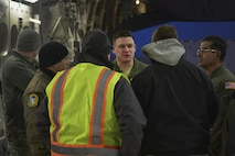Senior Airman Gabe Day, 729th Airlift Squadron loadmaster, speaks with his loadmaster team and members from Lockheed Martin during a briefing prior to loading a C-17 Globemaster III Nov. 30, 2016, at Buckley Air Force Base, Colo. Members from Lockheed Martin worked with an aircrew from the 729th Airlift Squadron to load a GPS non-flight satellite testbed prior to flying to Cape Canaveral, Florida. The GPS non-flight satellite testbed is a pathfinder vehicle used by the Space and Missile Systems Center to ensure future GPS III vehicles are adequately tested. (U.S. Air Force photo by Airman Holden S. Faul/ Released)