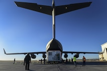 A C-17 Globemaster III remains taxied on the runway as members from Lockheed Martin and an aircrew from the 729th Airlift Squadron begin loading cargo Nov. 30, 2016, on Buckley Air Force Base, Colo. The members from Lockheed Martin and aircrew from the 729th Airlift Squadron loaded a GPS non-flight satellite testbed prior to flying to Cape Canaveral, Florida. The GPS non-flight satellite testbed is a pathfinder vehicle used by the Space and Missile Systems Center to ensure future GPS III vehicles are adequately tested. (U.S. Air Force photo by Airman Holden S. Faul/ Released)