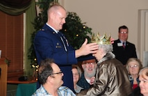 Lt. Col. Shane Lensgraf, 705th Munitions Squadron commander, crowns the Day of Love queen at Minot Air Force Base, N.D., Nov. 24, 2016. The Day of Love queen is presented to the oldest female in attendance at the event. (U.S. Air Force photo/Airman 1st Class Christian Sullivan)