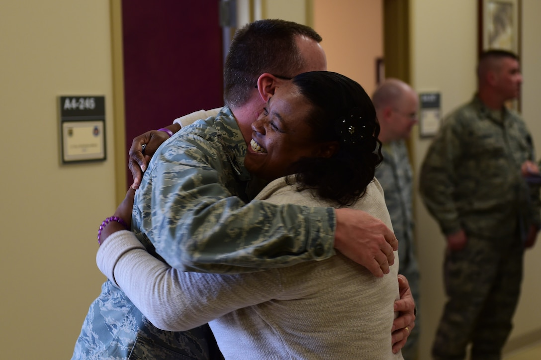 Pamela Parks, 460th Medical Group director of quality/risk management, hugs Col. John R. Andrus, Air Force Space Command Surgeon General, after receiving a coin Nov. 30th, 2016, at the Veterans Affairs Clinic in Aurora, Colo. Parks was awarded the coin for going above expectations to ensure the safety and readiness of our Airmen. (U.S. Air Force photo by Airman Jacob Deatherage/Released)