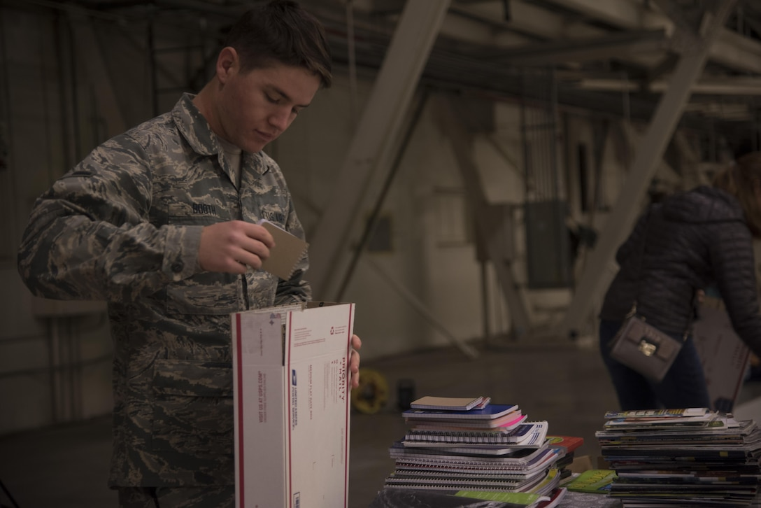 Airman Paul Booth, 92nd Aircraft Maintenance Squadron crew chief, places a notepad into a care package Dec. 1, 2016 at Fairchild Air Force Base. Booth volunteered to fill shipping boxes with various items such as soap, hot sauce, wet wipes and beef jerky. The boxes were packed as part of KREM 2 News Treats 2 Troops program that provides deployed military members with care packages. (U.S. Air Force photo/Senior Airman Nick J. Daniello)