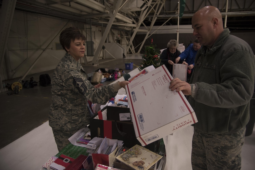 Chief Master Sgt. Shannon Rix, 92nd Air Refueling Wing command chief, and Master Sgt. Nicholas Ehman, 92nd Maintenance Squadron accessories flight assistant flight chief, pack letters into a shipping box Dec. 1, 2016 at Fairchild Air Force Base. Letters and other items were packed into boxes as part of KREM 2 News Treats 2 Troops program. Treats 2 Troops is a program that allows people to support deployed military members. (U.S. Air Force photo/Senior Airman Nick J. Daniello)