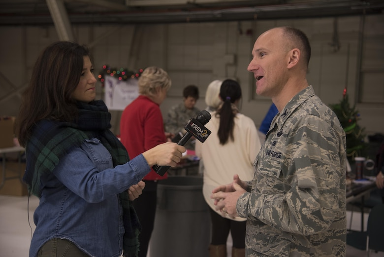 Laura Papetti, KREM 2 News anchor reporter, interviews Col. Ryan Samuelson, 92nd Air Refueling Wing commander, about Fairchild's involvement in the Treats 2 Troops program Dec. 1, 2016 at Fairchild Air Force Base. Team Fairchild volunteers packaged more than 400 care packages that will be delivered to deployed military members. (U.S. Air Force photo/Senior Airman Nick J. Daniello)