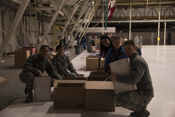 Team Fairchild volunteers pack items into care packages as part of KREM 2 News Treats 2 Troops program Dec. 1, 2016 at Fairchild Air Force Base. Volunteers packaged more than 400 boxes that will be delivered to deployed military members. The boxes are filled with various items, such as hot sauce, wet wipes, beef jerky, toothbrushes, and magazines. (U.S. Air Force photo/Senior Airman Nick J. Daniello)