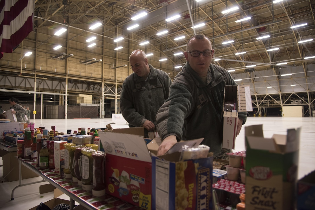 Master Sgt. Nicholas Ehman (left), 92nd Maintenance Squadron accessories flight assistant flight chief, and Master Sgt. Mark Simonds (right), Airman Family and Readiness Center superintendent, pack shipping boxes Dec. 1, 2016 at Fairchild Air Force Base. Ehman and Simonds were part of a team that consisted of more than 20 volunteers who packaged more than 400 shipping boxes. The care packages will be delivered to deployed military members as part of the KREM 2 News Treats 2 Troops program. (U.S. Air Force photo/Senior Airman Nick J. Daniello)