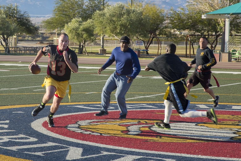 1st Lt. Andrew de Lannoy, combat engineer officer, Marine Wing Support Squadron 374, rushes the ball pass the staff noncommissioned officers' defensive line during the MWSS-374 Turkey Bowl at Felix Field aboard the Marine Corps Air Ground Combat Center, Twentynine Palms, Calif., Nov. 22, 2016. MWSS-374 held the Turkey Bowl to build camaraderie within the senior leadership. (Official Marine Corps photo by Lance Cpl. Dave Flores/Released)