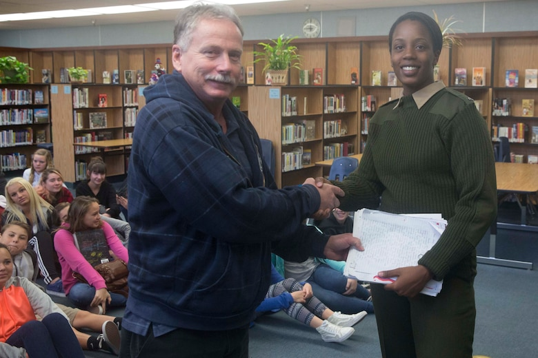 Cpl. Medina Ayala-Lo, combat correspondent, Headquarters Battalion, receives students' letters from Don Henry, a teacher at La Contenta Middle School, during a visit to answer student's questions in Yucca Valley, Calif., Nov. 30, 2016. Henry coordinates the event annually in an effort to teach his students about the military while giving them a chance to show their appreciation in the form of letters. (Official Marine Corps photo by Cpl. Julio McGraw/Released)