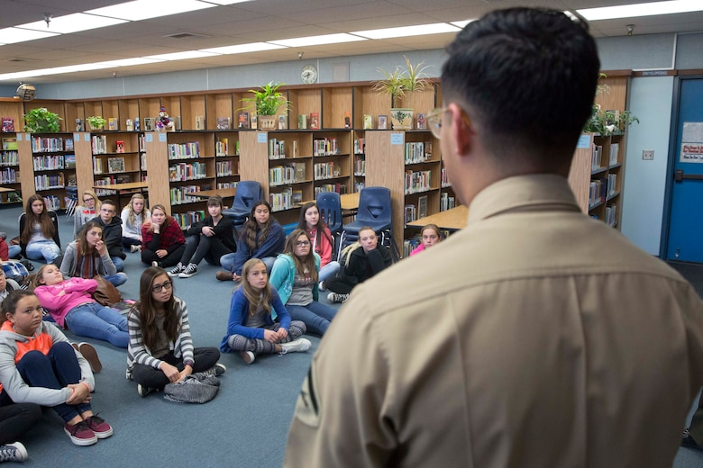 Lance Cpl. Dave Flores, combat correspondent, Headquarters Battalion, answers students' questions during a visit to La Contenta Middle School in Yucca Valley, Calif., Nov. 30, 2016. Don Henry, a teacher at the middle school, coordinates the event annually in an effort to teach his students about the military while giving them a chance to show their appreciation in the form of letters. (Official Marine Corps photo by Cpl. Medina Ayala-Lo/Released)
