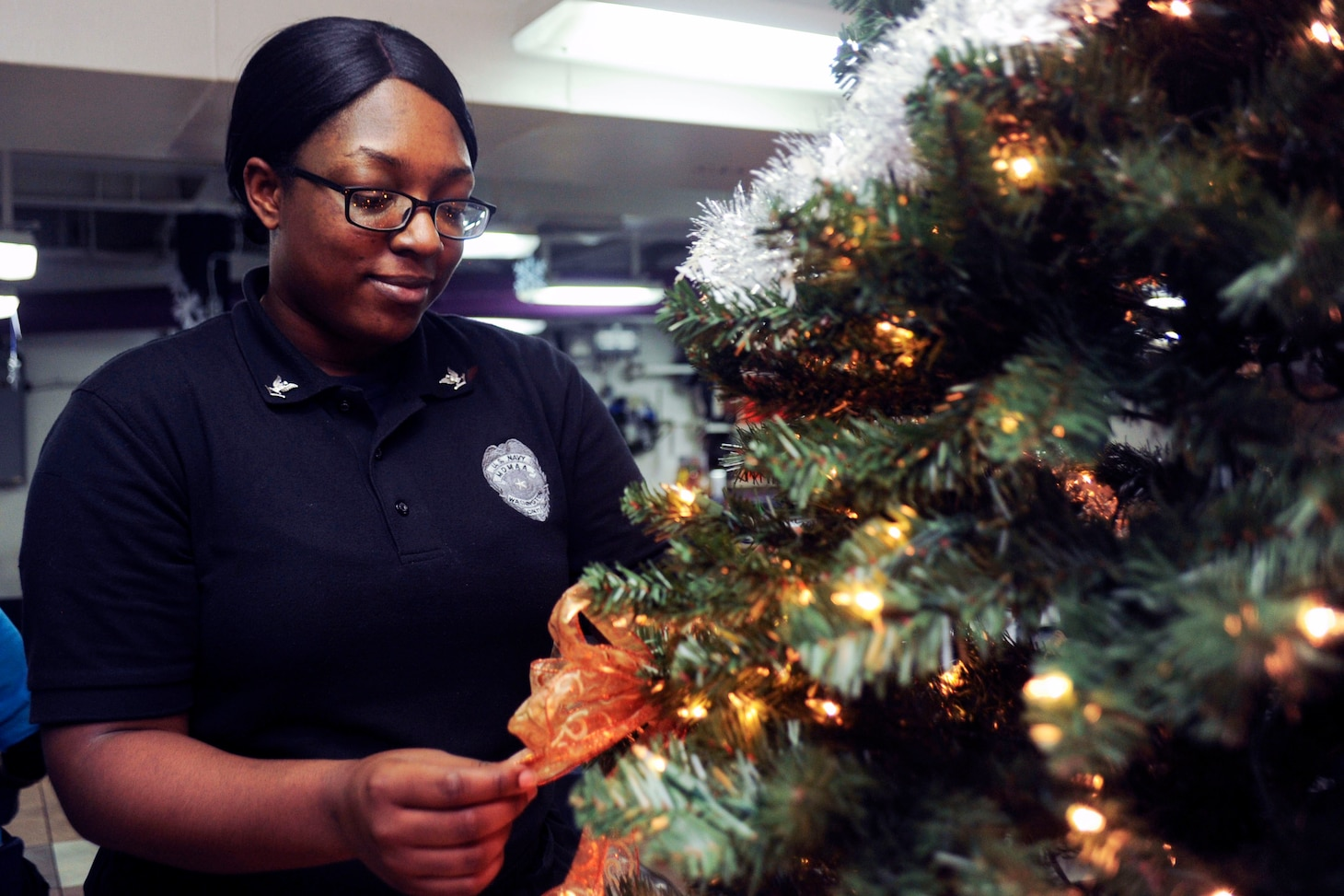Navy Petty Officer 3rd Class Taylor Bowie adjusts holiday decorations after a meal aboard the aircraft carrier USS George Washington in the Atlantic Ocean, Dec. 1, 2016. The George Washington, homeported in Norfolk, is underway conducting carrier qualifications in the Atlantic Ocean. Bowie is a mess deck master-at-arms. Navy photo by Petty Officer 3rd Class Alora R. Blosch