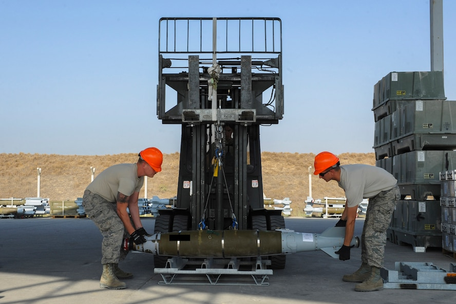 U.S. Air Force Senior Airman Ross and Staff Sgt. Benjamin, both 447th Expeditionary Aircraft Maintenance Squadron munitions systems journeymen, lower a GBU-54 Laser Joint Direct Attack Munition bomb onto a storage pallet Oct. 29, 2016, at Incirlik Air Base, Turkey. The bombs will be taken to another location to be tested for serviceability. (U.S. Air Force photo by Airman 1st Class Devin M. Rumbaugh) (Portions of this image are blocked for security concerns)