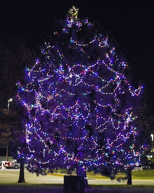 The holiday tree glows in front of the Mission's End Club during the annual tree lighting event at Whiteman Air Force Base, Mo., Nov. 29, 2016. Approximately 1,400 people attended the wizard-themed event that kicked off the holidays in a magical way.