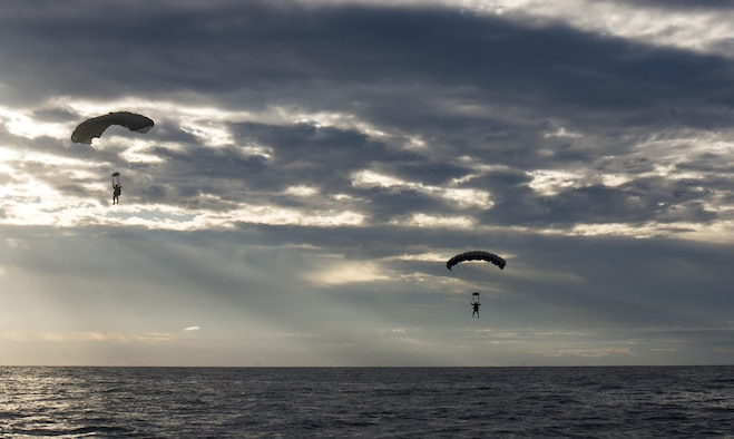 Airmen from the 320th Special Tactics Squadron at Kadena Air Base, Japan, parachute into the Pacific Ocean at dawn Nov. 22, 2016, off the western coast Okinawa, Japan. The 320th STS Airmen train to operate in adverse conditions at sea or overland to accomplish their mission. (U.S. Air Force photo/Senior Airman Omari Bernard)
