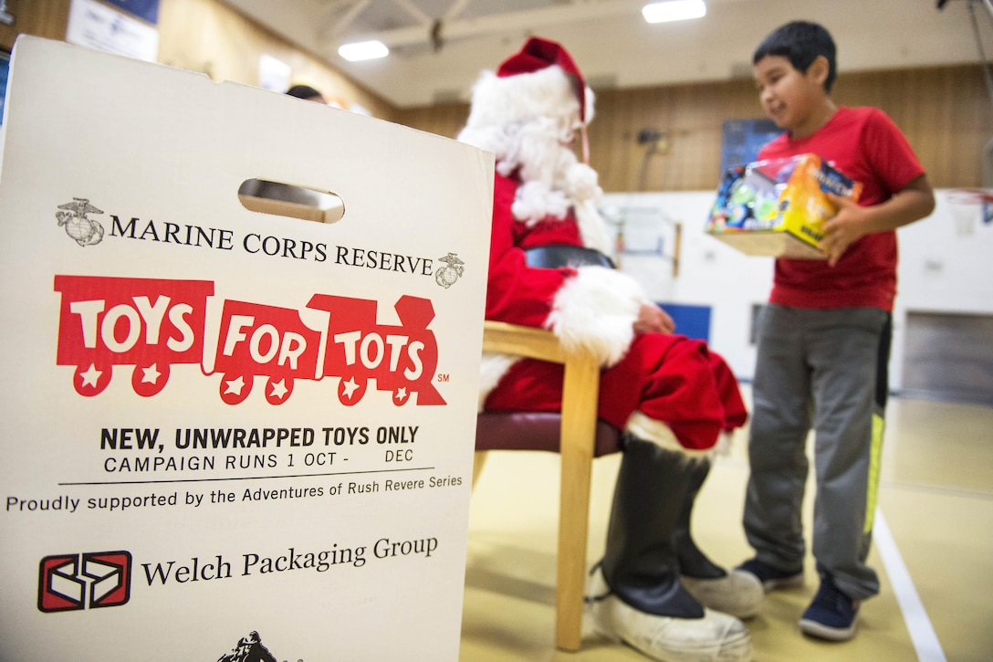 Santa Claus hands out presents to children during Toys for Tots at Nunachiam Sissauni School in Buckland, Alaska, Nov. 29, 2016. Santa was assisted by by Marine Corps 1st Sgt. Joshua Guffey, the inspector-instructor first sergeant assigned to Detachment Delta, 4th Law Enforcement Battalion. Air Force photo by Alejandro Pena