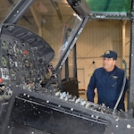 "Sergeant Jerry King, a pilot with the Michigan State Police Aviation unit, looks over the controls of the UH-1 ""Huey"" Iroquois helicopter that came from the Army via the DLA Disposition Services Law Enforcement Support Office."