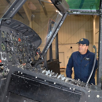 """Sergeant Jerry King, a pilot with the Michigan State Police Aviation unit, looks over the controls of the UH-1 """"Huey"""" Iroquois helicopter that came from the Army via the DLA Disposition Services Law Enforcement Support Office."""