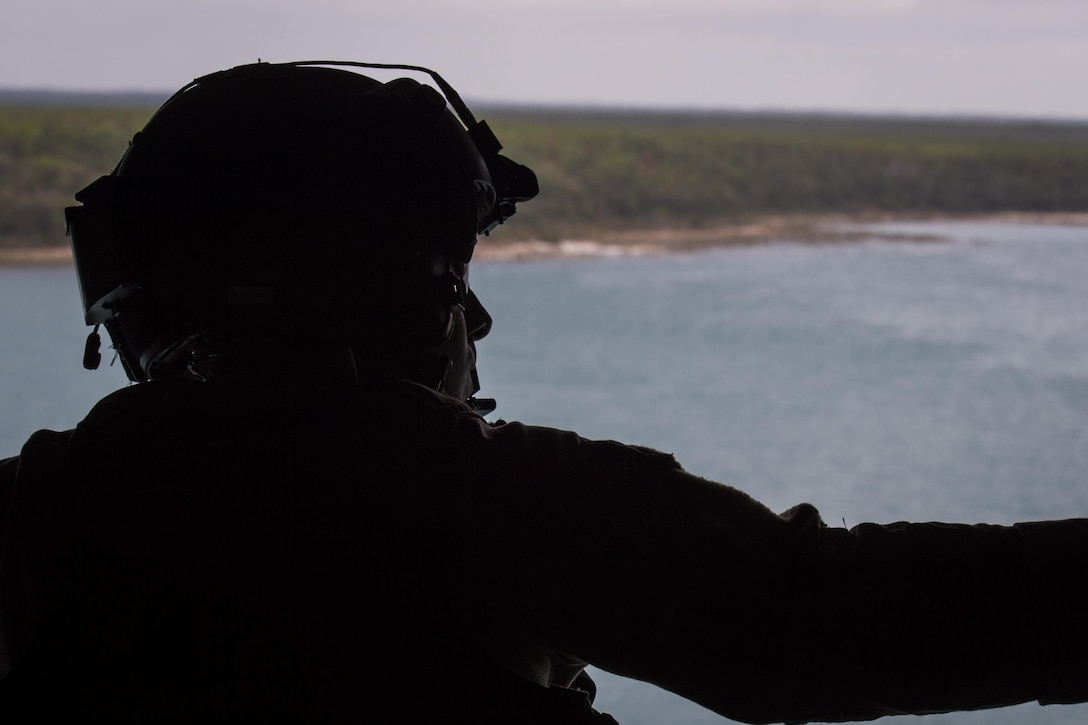 A flight engineer with the 8th Special Operations Squadron looks out at the Eglin Range, Fla., Nov. 30, 2016. Air Commandos with the 8th SOS conduct water training to maintain relevance for tomorrow and ensure readiness for global special operations. (U.S. Air Force photo by Airman 1st Class Joseph Pick)