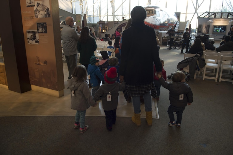 Children are guided toward the U.S. Air Force's premier rock band, Max Impact, at the Smithsonian National Air and Space Museum in Washington, D.C., Dec. 2, 2016. The band played a variety of holiday favorites for their audience and those passing by. (U.S. Air Force photo by Senior Airman Mariah Haddenham)