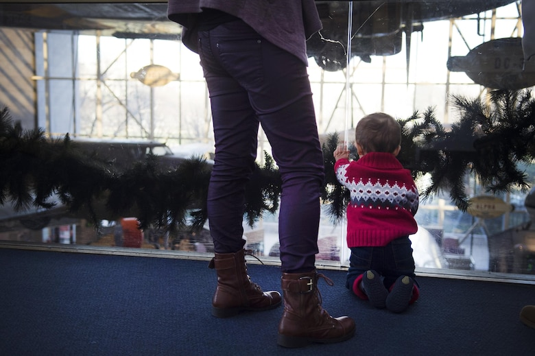 A child watches the U.S. Air Force's premier rock band, Max Impact, from the second floor of the Smithsonian National Air and Space Museum in Washington, D.C., Dec. 2, 2016. The band performed several times throughout the afternoon, playing several holiday favorites. (U.S. Air Force photo by Senior Airman Mariah Haddenham)