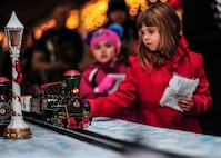 Children watch a model train pass by during the Starry, Snowy, Southwest Night holiday celebration at Davis-Monthan Air Force Base, Ariz., Dec. 1, 2016. Desert Lightning Team members and their families were invited to enjoy free hot chocolate and cookies while participating in festivities such as photos with Santa, a giant rocking horse, a mechanical snowboard, arts and crafts and much more. (U.S. Air Force photo by Airman Nathan H. Barbour)