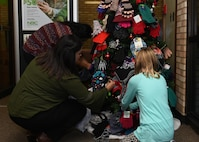 Employees at the Altus Air Force Base branch of the National Bank of Commerce decorate a holiday tree with hats and gloves during the Mitten Tree event, Nov. 29, 2016, at Altus Air Force Base, Okla. This event is held annually to collect cold weather clothing for children in the local community. (U.S. Air Force photo by Airman 1st Class Kirby Turbak/Released)