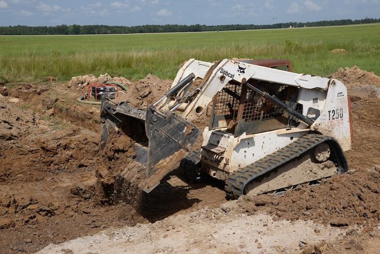 Senior Airman Nathaniel Henkel, 823rd Rapid Engineer Deployable Heavy Operational Repair Squadron, Engineering, Hurlburt Field, Florida, clears a lane of dirt on the flightline of Columbus Air Force Base, Mississippi, July 12. REDHORSE estimates the RSU project will be completed within two weeks. (U.S. Air Force photo/Airman 1st Class John Day)