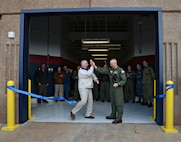 Scott Appleton, with HGL Construction in Midwest City, left, and Capt. Ed McCabe, commander of Strategic Communications Wing ONE and Task Force 124, cut the ceremonial ribbon Nov. 22, officially opening Bldg. 824, TACAMO's newest hangar. The 36,000-square-foot building will be able to accommodate depot-level maintenance on the Navy's E-6B Mercury. (Air Force photo by Kelly White)