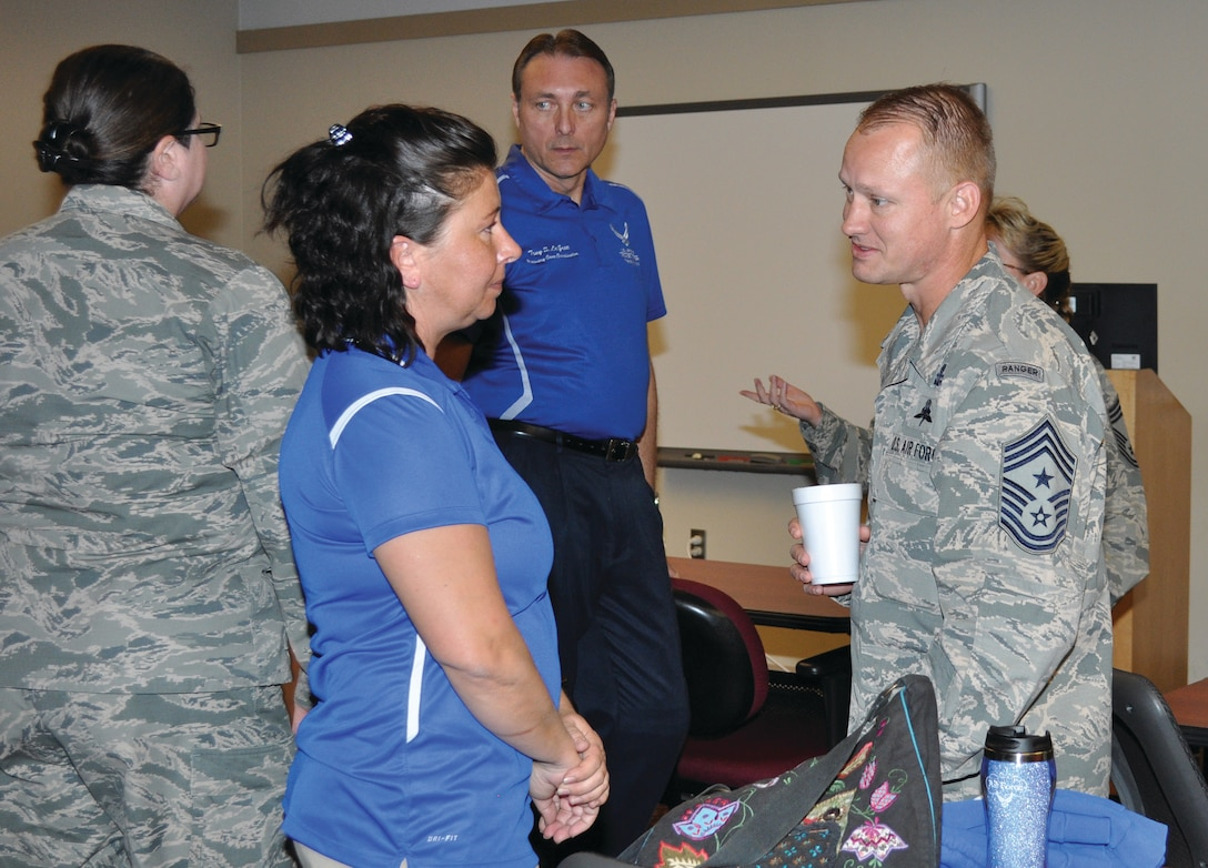 Retired Master Sgt. Lisa Hodgden talks to 552nd Air Control Wing Command Chief Master Sgt. Mark Hurst after an inspiring talk about her ordeals. Air Force Recovery Care Coordinator, Tony LaGree, stands in the background. (Air Force photo by Kimberly Woodruff)