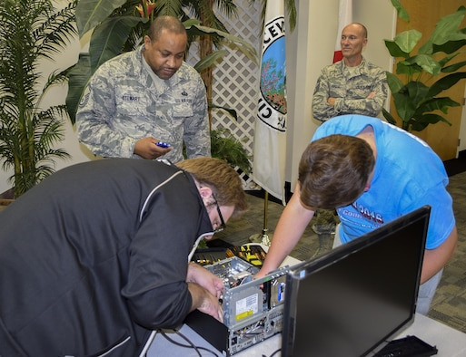 Members of the 919th Special Operations Communications Squadron watch and keep time while kids put together a desktop computer at this year's Tech Bowl in Niceville Fla., Nov. 5.  The reservists acted as timekeepers and judges for the youth competition.  (Courtesy photo)