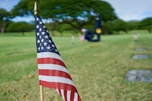 In the distance, U.S. Air Force Staff Sgt. Johnnie Anderson and Airman 1st Class Andrew Titus, dental technicians with the 15th Aeromedical Squadron, place a commemorative U.S. flag at a gravemarker at the National Memorial Cemetery of the Pacific, Honolulu, Hawaii, Dec. 3, 2016. Anderson and Titus placed multiple flags during a commemoration ceremony honoring the courage, service and sacrifice of the U.S. military personnel who died during the attacks on Pearl Harbor and Oahu on Dec. 7, 1941. Dec. 7, 2016 marks the 75th anniversary of the attacks and the U.S. military and the State of Hawaii are hosting a series of remembrance events to honor the Pacific Theater's veterans. (U.S. Air Force photo by Tech. Sgt. James Stewart/Released)