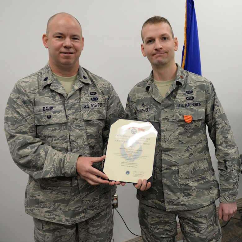 U.S. Air Force Lt. Col. William Davis, 157th Air Refueling Wing vice wing commander, left, presents the Air Force Combat Action Medal to Maj. Scott M. Treadwell, 157th Comptroller Flight, commander, Pease Air National Guard Base, N.H., Dec. 3, 2016.  Treadwell received the award for participation in combat in connection with military operations Sept. 25, 2005 while serving as a first lieutenant in the U.S. Army during Operation Iraqi Freedom. (U.S. Air National Guard photo by Staff Sgt. Curtis J. Lenz)