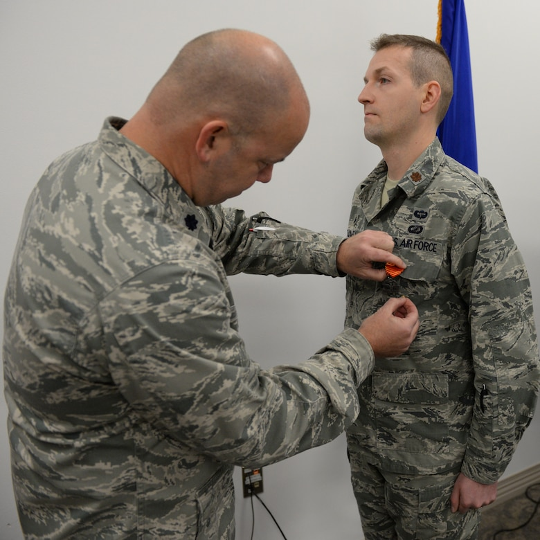 U.S. Air Force Lt. Col. William Davis, 157th Air Refueling Wing vice wing commander, left, presents the Air Force Combat Action Medal to Maj. Scott M. Treadwell, 157th Comptroller Flight commander, Pease Air National Guard Base, N.H., Dec. 3, 2016.  Treadwell received the award for participation in combat in connection with military operations Sept. 25, 2005 while serving as a first lieutenant in the U.S. Army during Operation Iraqi Freedom. (U.S. Air National Guard photo by Staff Sgt. Curtis J. Lenz)