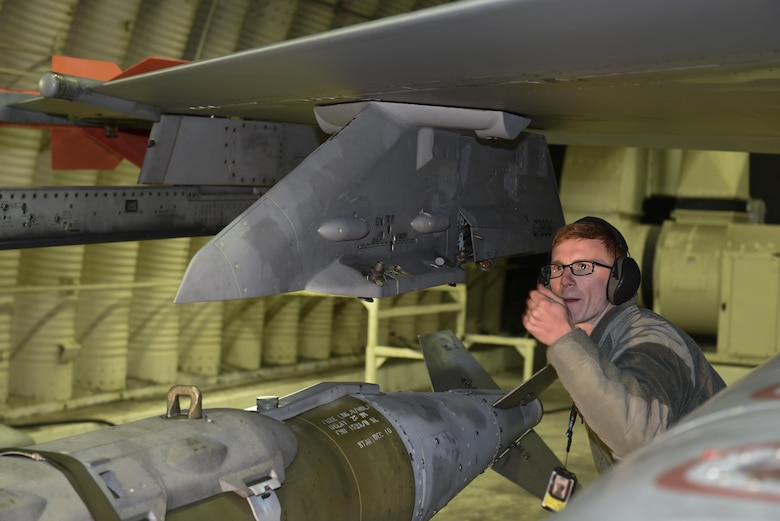 Staff Sgt. Kenneth Gullette, 35th Aircraft Maintenance Unit weapons load crew chief, guides a Joint Direct Attack Munition GBU-31 onto the wing of an F-16 Fighting Falcon at Kunsan Air Base, Republic of Korea, Nov. 30, 2016. Members of the 35th AMU safely prepare F-16's for a variety of missions, which feed into the 8th Fighter Wings priorities of defending the base and being postured to respond to any threats. (U.S. Air Force photo by Senior Airman Michael Hunsaker/Released)