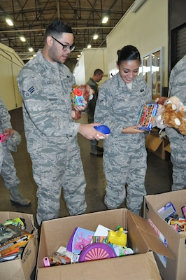 (Left) Senior Airman Eddie Castillo and Airman Ashley Garcia, both 433rd Force Support Squadron services technicians, find the perfect gifts to fill stockings during a free stocking stuffer giveaway at Joint Base San Antonio-Lackland, Texas Dec. 3, 2016.  The gifts were donated by Operation Homefront, who donate millions of toys each year to military families during the holiday season. (U.S. Air Force photo/Senior Airman Bryan Swink)