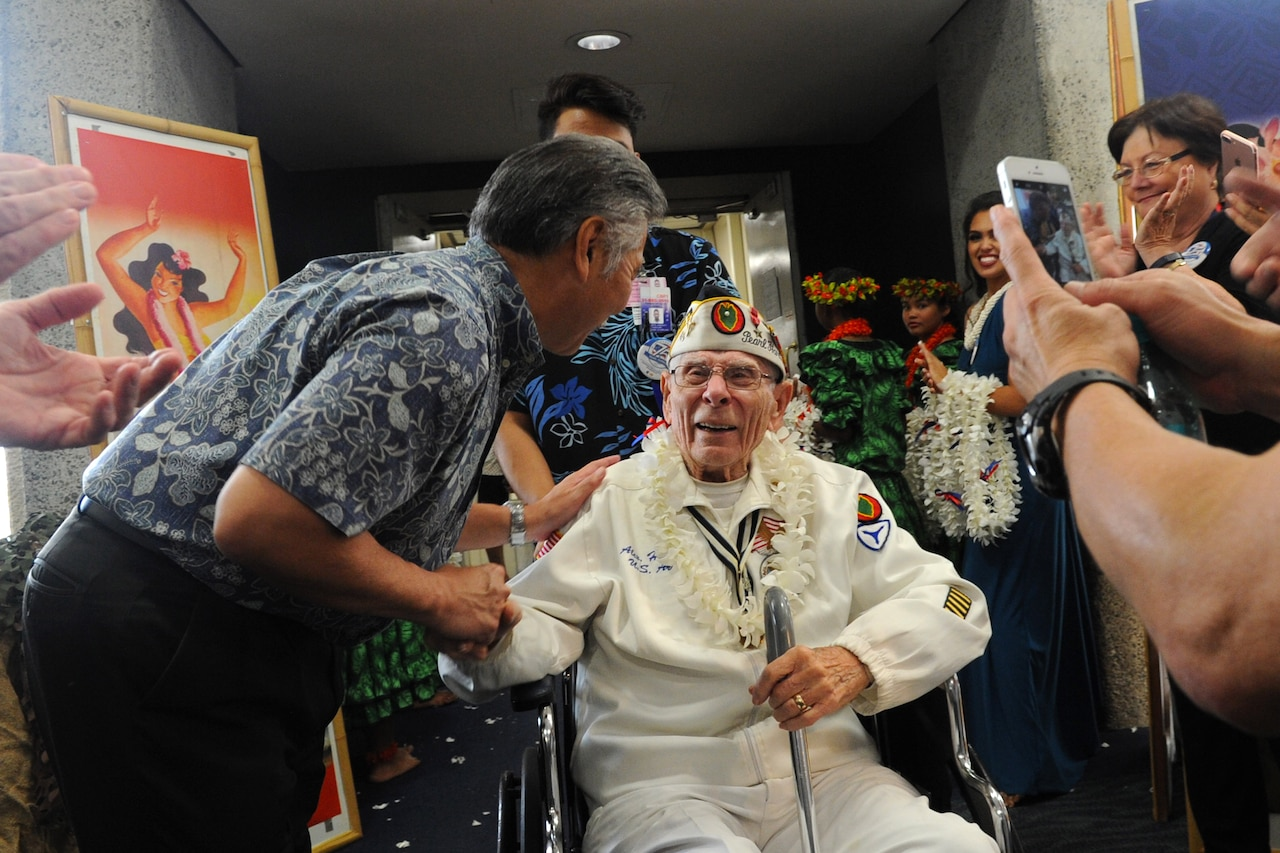 The governor of Hawaii, David Ige, greets Pearl Harbor survivor and former soldier Alexander Horanzy upon arrival at Honolulu, Dec. 3, 2016. Horanzy was on an honor flight from Los Angeles that carried 32 Pearl Harbor survivors and other veterans to Hawaii for commemorations for the 75th anniversary of the infamous attack. DoD photo by Lisa Ferdinando