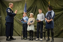 JOINT BASE ELMENDORF-RICHARDSON, Alaska -- Chief Master Sgt. Paul Bear Barendregt, a pararescueman and chief enlisted manager for the Alaska Air National Guard's 212th Rescue Squadron, applauds after presenting his three children with American flags during his retirement ceremony at the 212th's headquarters building here Dec. 3, 2016. Through his skill and commitment Barendregt exemplified the motto of the Air Force Pararescueman: These things we do, that others may live. (U.S. Air National Guard photo by Staff Sgt. Edward Eagerton/released)