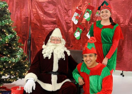 Victoria Fillipi, a member of the Iowa Guard Youth Council and Staff Sgt. Damian Huizar, a services Airmen assigned to the 185th Air Refueling Wing, pose for a photo with Santa at Sioux City Iowa, Dec. 3, 2016. Children got the opportunity to take their photo with Santa and play games as a part of Operation Santa's Sleigh. (Iowa Air National Guard photo by Staff Sgt. Ter Haar/Released)
