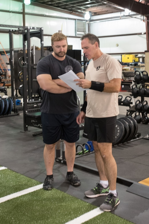 Lt. Col. Sean McLane, commander of the 123rd Special Tactics Squadron, looks over his personal workout and rehabilitation regimen during a session at the Human Performance Program facility on the Kentucky Air National Guard Base in Louisville, Ky., Oct. 14, 2016. Evaluating his progress is Will Lawson, the program's lead athletic trainer and strength coach, who helped design McLane's daily workout routine. (U.S. Air National Guard photo by Tech. Sgt. Vicky Spesard)