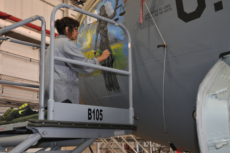 Donna Mrdjenovich paints nose art on a KC-135 aircraft near Pittsburgh Pennsylvania July 29, 2016 (U.S. Air National Guard Photo by Tech. Sgt. Michael Fariss)