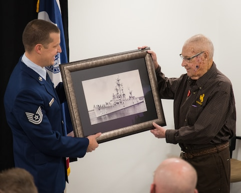 U.S. Air Force Tech. Sgt. Bryce Bishop and his grandfather, Kenneth Murphy, pose for a picture during a medal presentation ceremony, Dec. 3, 2016 at Cheyenne Air National Guard base in Cheyenne, Wyoming. Murphy was awarded the Ambassador for Peace Medal for his service aboard the USS Harveson (DE) as a U.S. Navy gunners mate during the Korean War. (U.S. Air National Guard photo by Tech. Sgt. John Galvin/released)