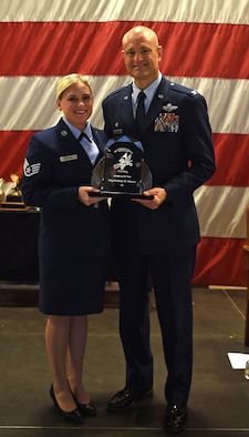 Staff Sgt. Kortney M. Mazera receives the 132d Wing Airman of the Year Award from Col. Shawn Ford, commander 132d Wing on November 5, 2016 at the Des Moines Airbase. The award presentation was part of the 132d Wing's annual awards ceremony. (U.S. Air National Guard photo by Staff Sgt. Michael J. Kelly)