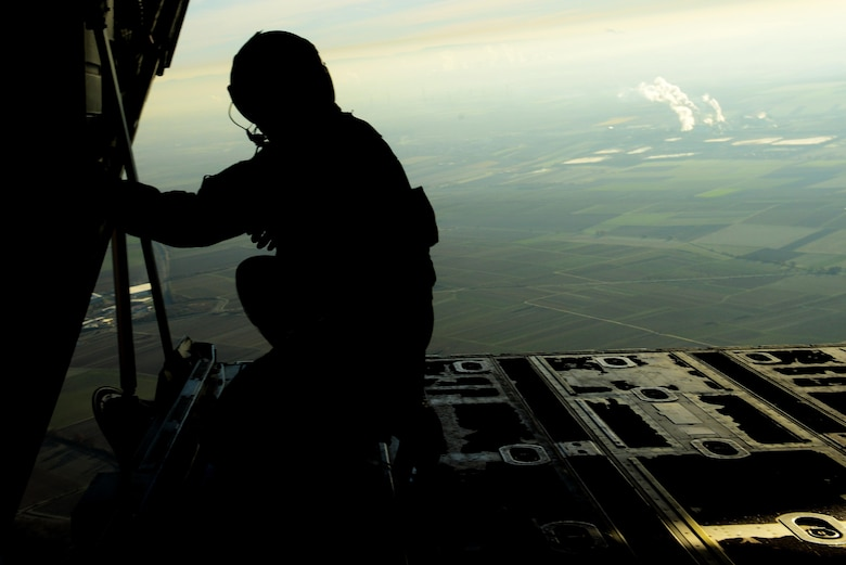 U.S. Air Force Senior Airman Patrick Cassidy, 37th Airlift Squadron loadmaster, peers out the back of a C-130J Super Hercules after air dropping more than 50 paratroopers over the skies of Germany, Nov. 30, 2016. The crew, stationed at Ramstein Air Base, assisted in International Jump Week by providing aircraft for the paratroopers to jump from. (U.S. Air Force photo by Senior Airman Jonathan Bass)