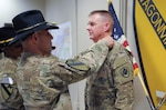 Army Col. Chris Colavita presents the Combat Action Badge to Col. Rick Ellis for his lifesaving actions on the battlefield.