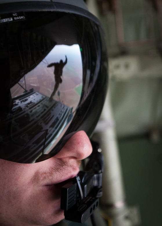 Senior Airman Patrick Cassidy, 37th Airlift Squadron loadmaster, observes as NATO allied nation paratroopers jump out of a C-130J Super Hercules during an International Jump Week exercise over Germany Dec. 1, 2016. Cassidy and the rest of the crew, stationed at Ramstein Air Base, assisted in the exercise by providing aircraft for the paratroopers to jump from. (U.S. Air Force photo by Airman 1st Class Lane T. Plummer)